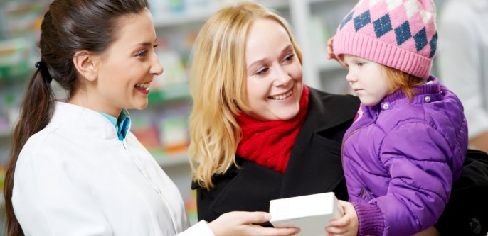Pharmacist giving a box to the child